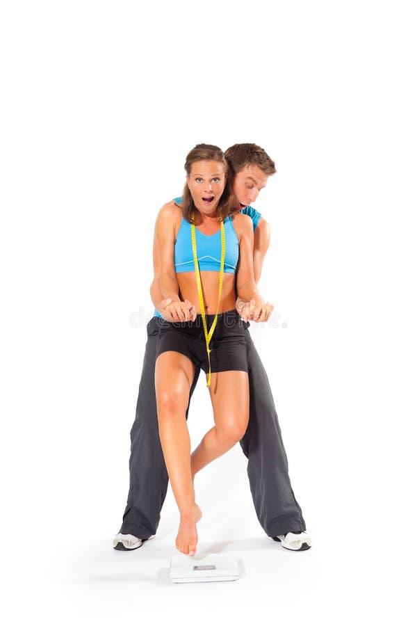 Женщина молодого человека поднимаясь над веся масштабом стоковые фотографии rf