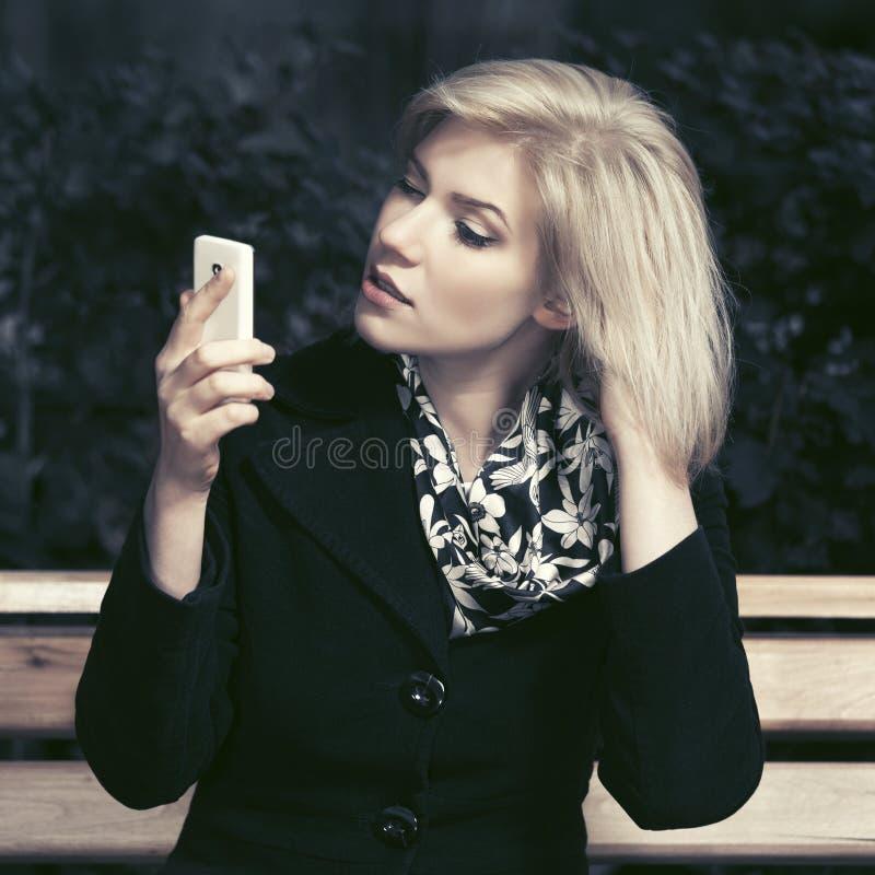 Женщина молодой моды белокурая используя умный телефон в улице города стоковые изображения
