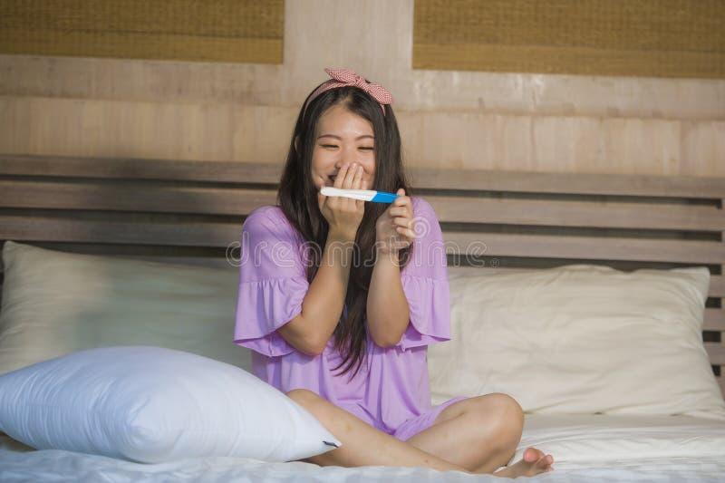 Женщина молодой счастливой возбужденной беременной азиатская корейская дома держа упредитель и проверяя позитивный результат на т стоковая фотография