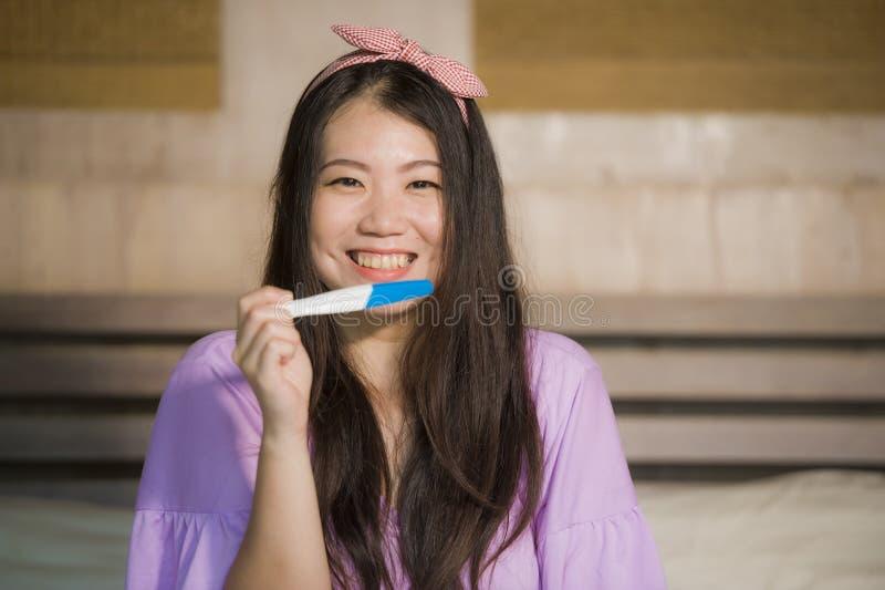 Женщина молодой счастливой возбужденной беременной азиатская корейская дома держа упредитель и проверяя позитивный результат на т стоковые изображения
