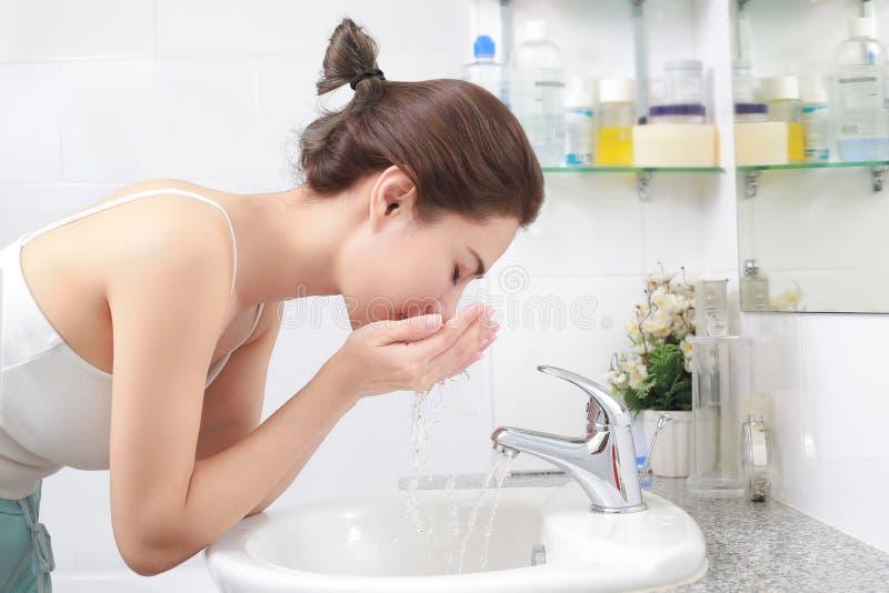 Женщина моя ее сторону с водой над раковиной ванной комнаты стоковые фотографии rf