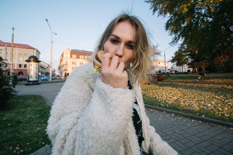 Женщина молодой моды смешная есть гамбургер внешний на улице стоковая фотография