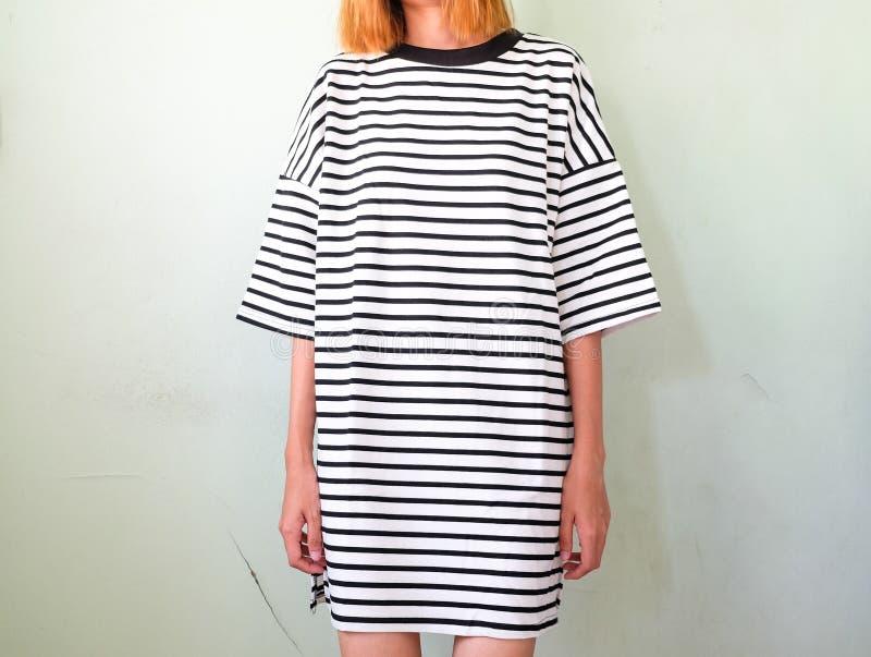 Женщина моды в striped платье на белой стене стоковая фотография