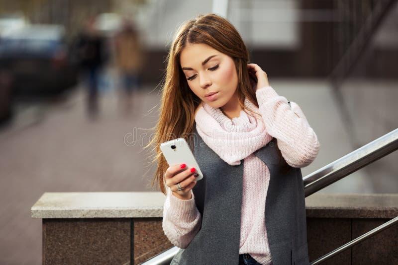 Женщина моды используя smartphone на улице города стоковое фото