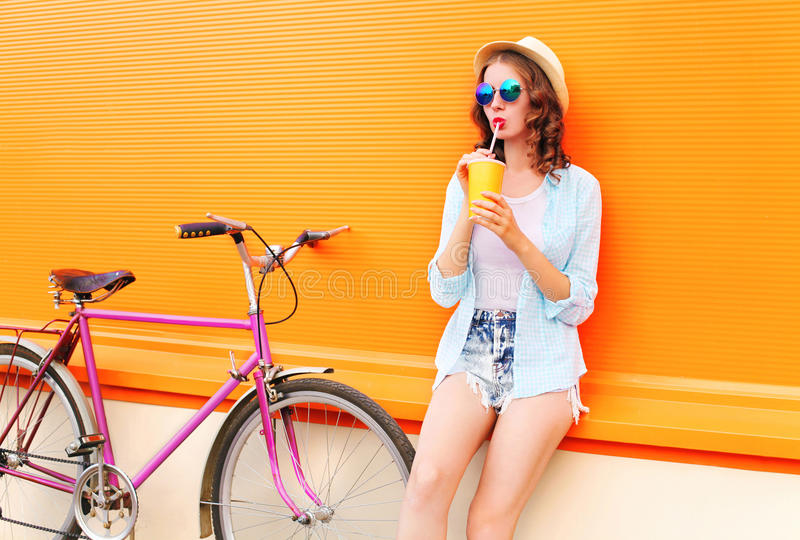 Женщина моды милая выпивает фруктовый сок от чашки с ретро велосипедом над красочным апельсином стоковые фотографии rf
