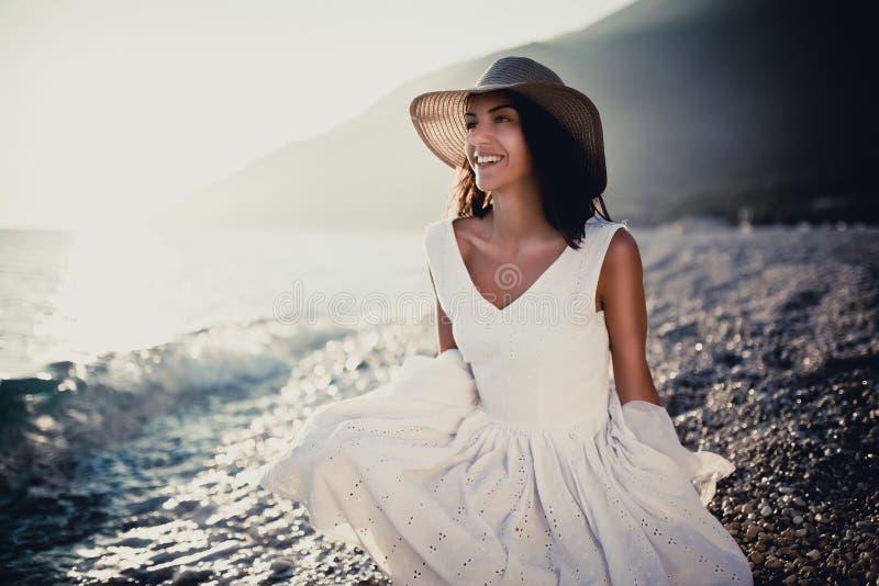 Женщина моды пляжа лета в белом платье наслаждаясь летом и солнцем, идя пляж около голубого моря Расслабленная эмоциональная чувс стоковые фотографии rf