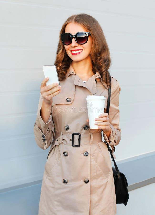 Женщина моды симпатичная элегантная молодая усмехаясь используя smartphone держит муфту сумки пальто кофейной чашки нося в городе стоковое изображение