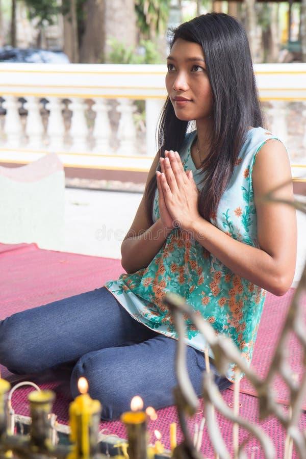 Женщина моля на статуе Будды стоковое изображение rf