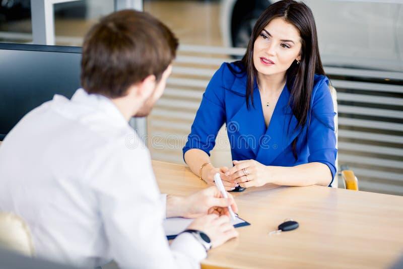 Женщина мужчины и клиента продавца в автомобиле продает офис в розницу стоковое фото