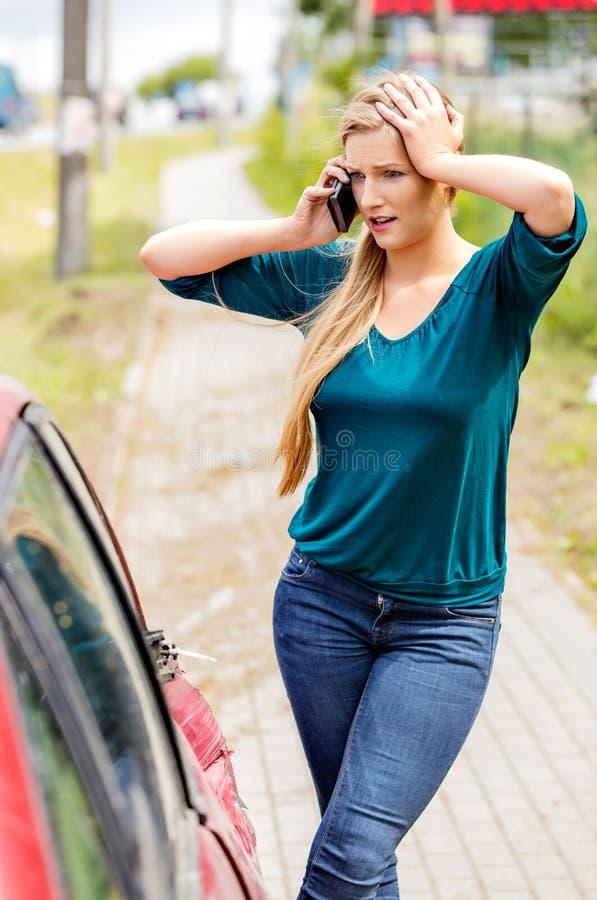 Женщина набирая ее телефон после автокатастрофы стоковое фото