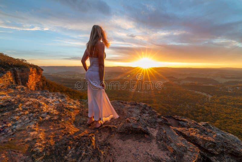 Женщина наблюдая блаженные заходы солнца от спрятанных уступов скалы стоковое фото