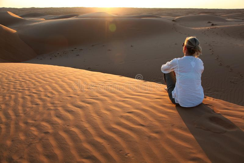 Женщина наблюдая заход солнца на красных песчанных дюнах Омана стоковые фото