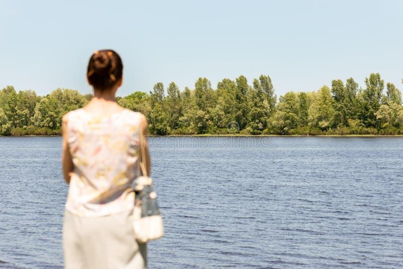 Женщина наблюдая к реке стоковые изображения
