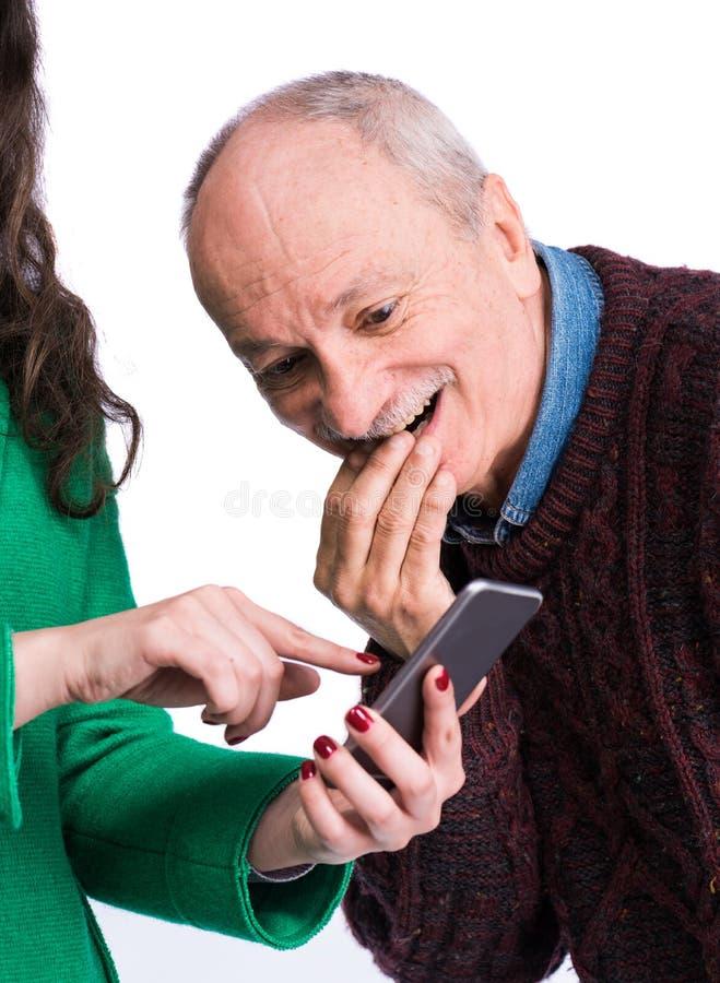 Женщина наблюдая умный телефон с удивленным и изумленным человеком стоковые изображения
