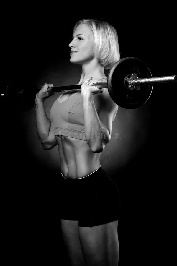 Женщина нагнетая вверх muscules с гантелями стоковое фото rf