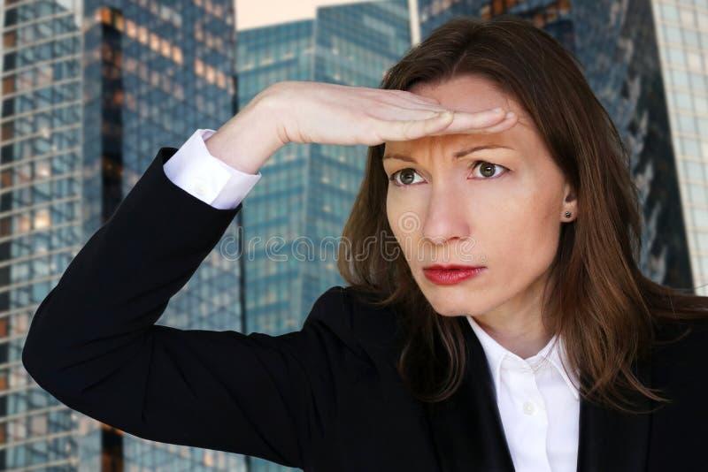 Женщина надежды смотря вперед с рукой в руководителе бизнеса офиса лба стоковое изображение