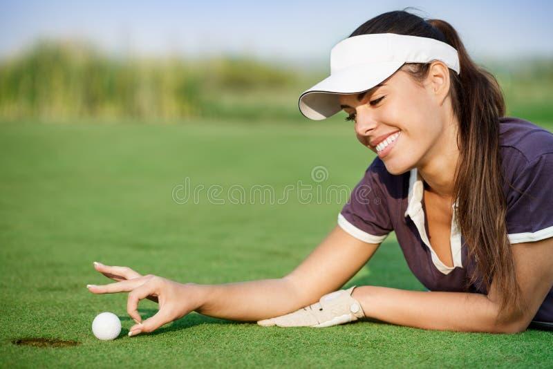 Женщина нажимая шар для игры в гольф стоковая фотография