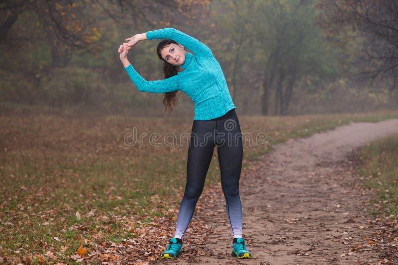 Женщина, наклоняющаяся бок о бок с поднятыми руками в лесу стоковое изображение
