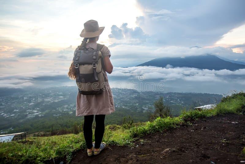 Женщина наслаждаясь восходом солнца от верхней части горы Batur, Бали, Индонезии стоковые фото