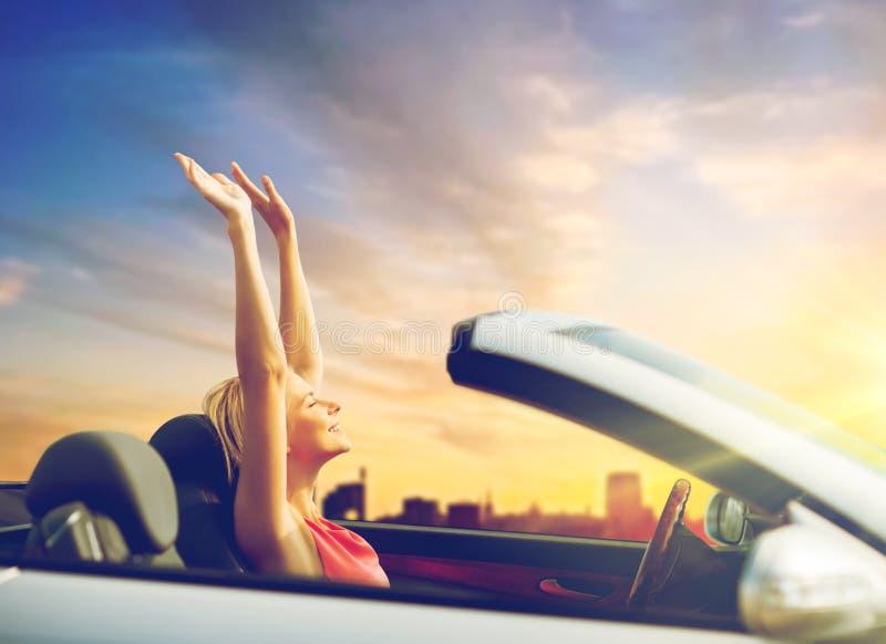 Женщина наслаждаясь заходом солнца в обратимом автомобиле над городом стоковая фотография rf
