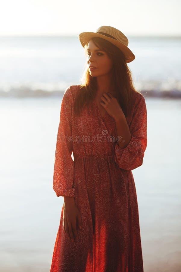 Женщина наслаждаясь красивым заходом солнца на пляже стоковые изображения rf
