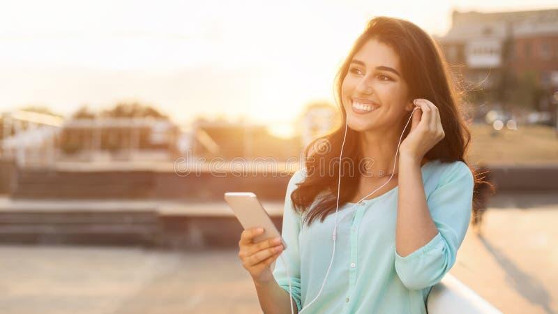 Женщина наслаждаясь музыкой в наушниках, имеющ прогулку в городе стоковые фото