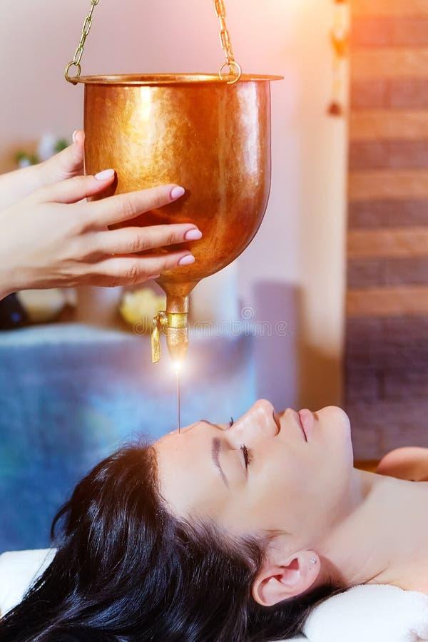 Женщина наслаждаясь обработкой массажа масла Ayurveda в курорте стоковое фото rf