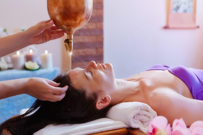 Женщина наслаждаясь обработкой массажа масла Ayurveda в курорте стоковые изображения rf