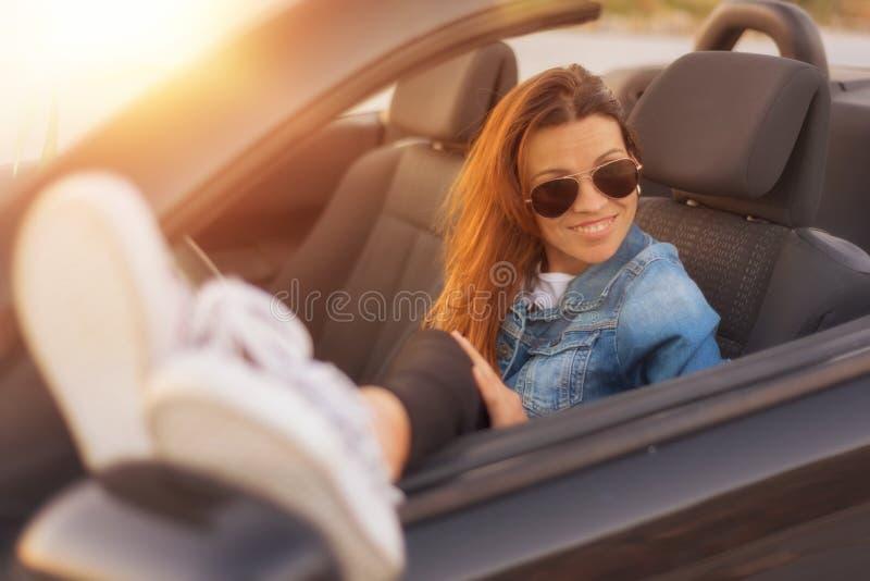 Женщина наслаждаясь обратимым автомобилем на заходе солнца стоковое фото rf