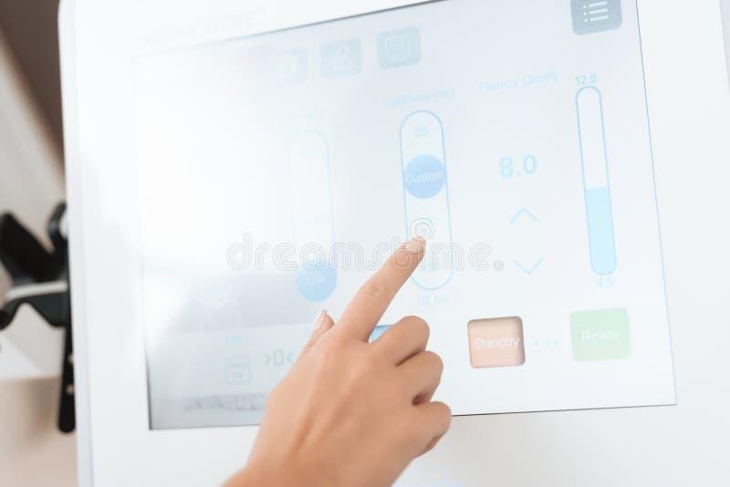 Женщина настраивает машину удаления волос лазера Оно устанавливает работающий режим на экране касания стоковые изображения rf