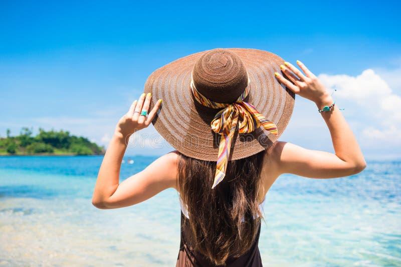 Женщина наслаждаясь взглядом на пляже или океане стоковое фото