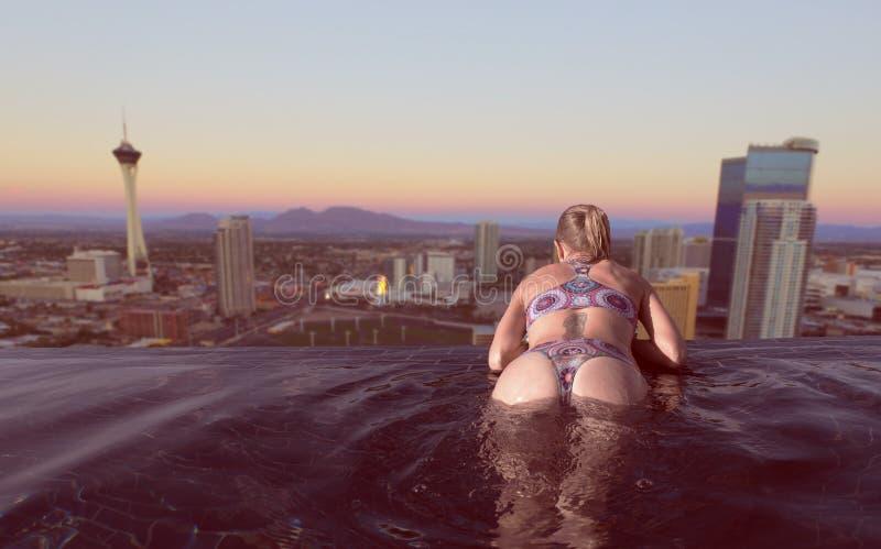 Женщина наслаждаясь видом на город Лас-Вегас от пейзажного бассейна стоковое изображение