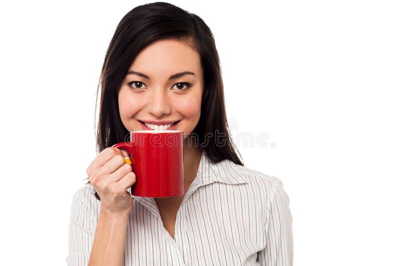 Женщина наслаждаясь кофе во время пролома работы стоковые фото