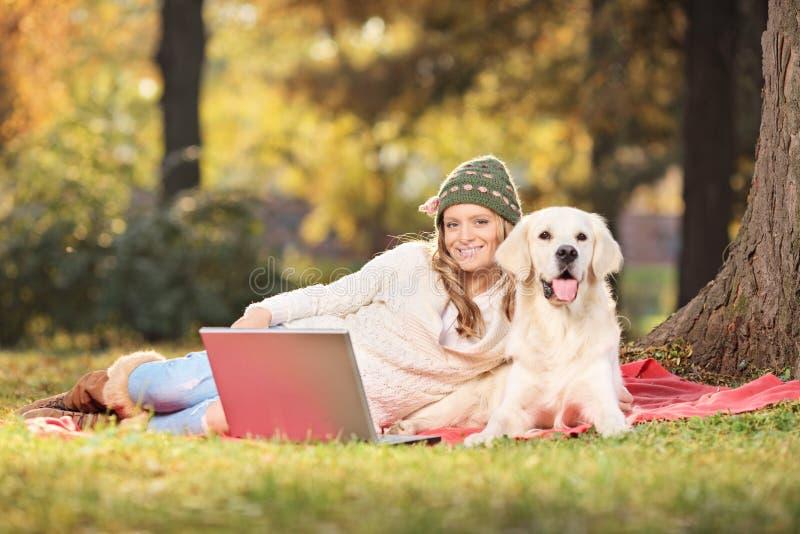 Женщина наслаждаясь пикником с ее собакой в парке стоковое изображение rf