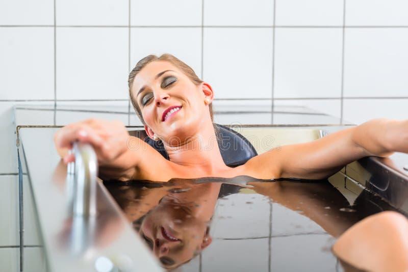 женщина наслаждаясь терапией альтернативы ванны грязи стоковая фотография rf