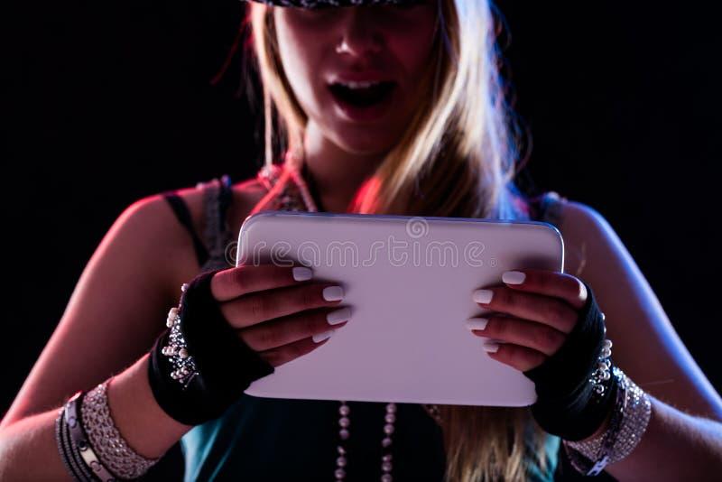 Женщина наслаждаясь цифровым информационным наполнением на таблетке стоковое изображение