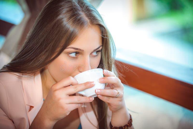 Женщина наслаждаясь чашкой кофе в кафе стоковые изображения