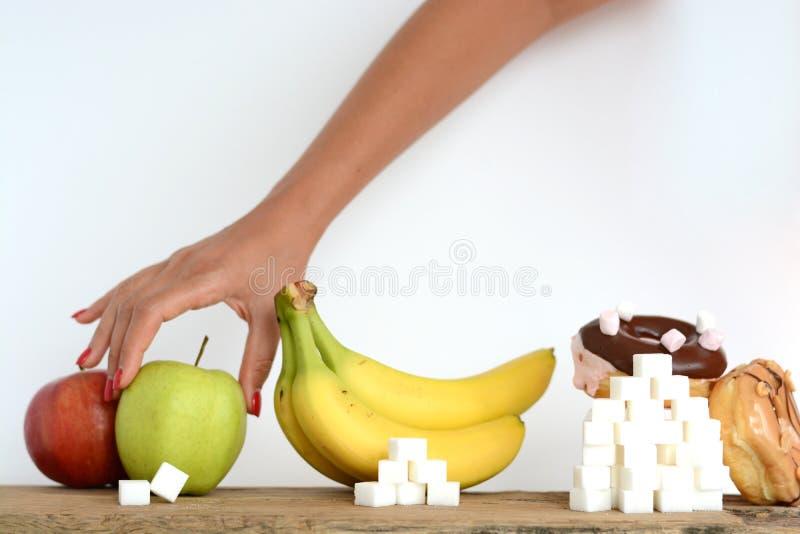 Женщина на †диеты «выбирая съесть здоровую, между свежими фруктами и помадками стоковые фотографии rf