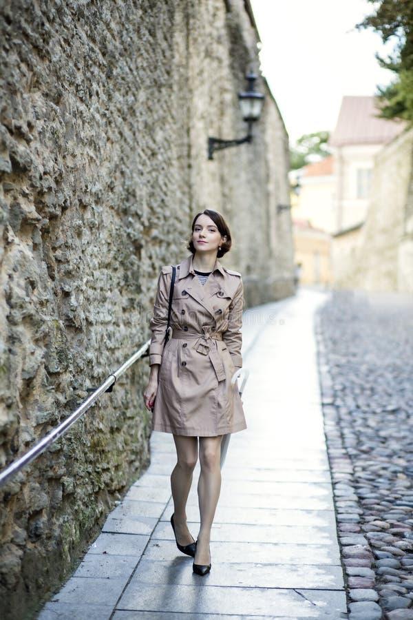 Женщина на бежевом пальто около старой стены города стоковые изображения rf