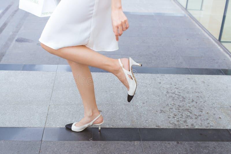 Женщина на высоких пятках имеет затруднения, который нужно идти в ее ботинки стоковая фотография rf