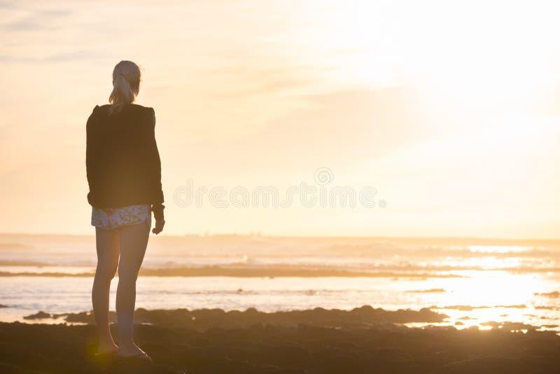 Женщина на заходе солнца песчаного пляжа наблюдая стоковые фото