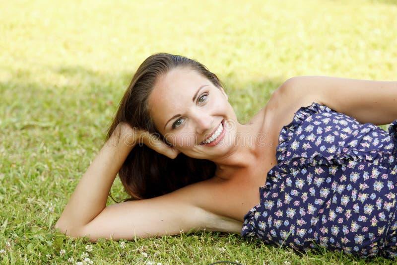 Женщина на зеленой траве стоковое изображение