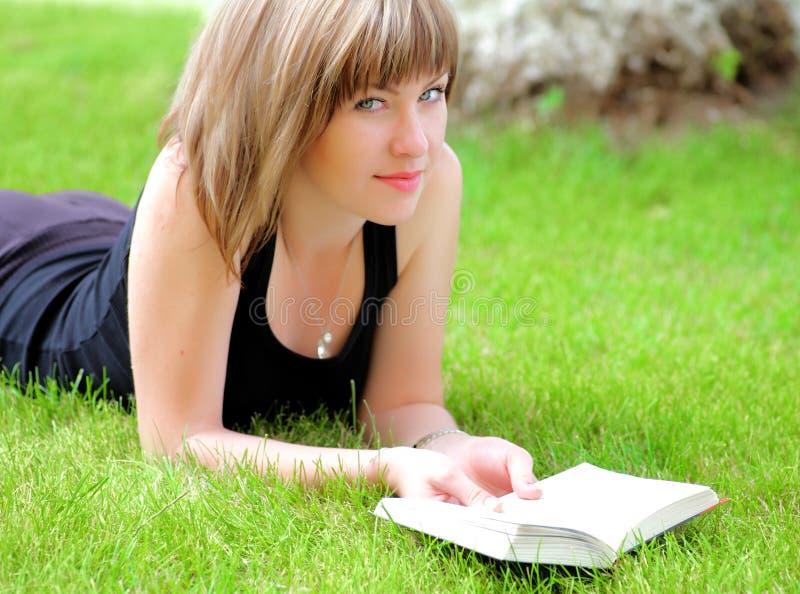 Женщина на книге чтения травы стоковые фото