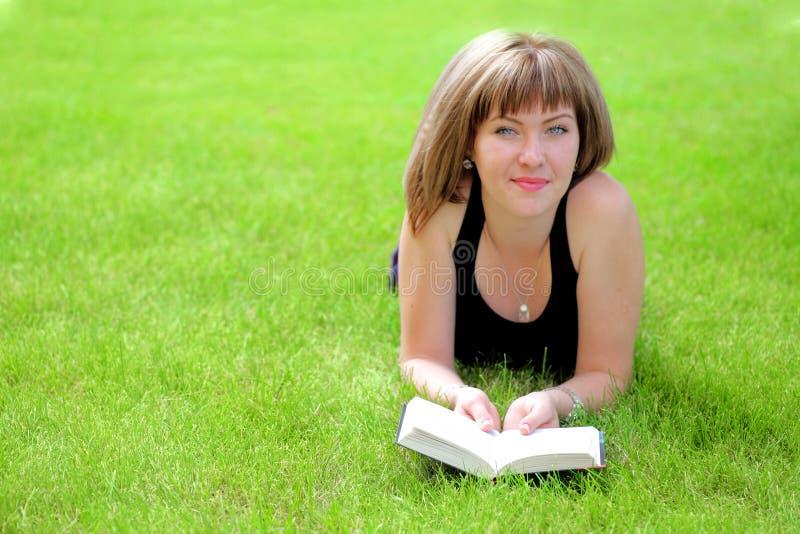 Женщина на книге чтения травы стоковые изображения