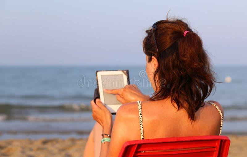 Женщина на красном стуле читает ebook на пляже морем стоковая фотография rf