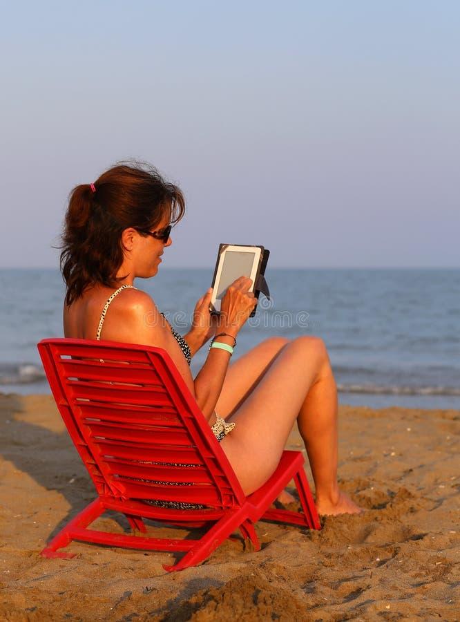 Женщина на красном стуле читает ebook стоковая фотография rf