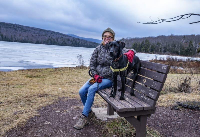 Женщина на озере с собакой в зиме стоковое фото rf