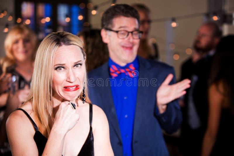 Женщина на партии с Boorish человеком стоковое изображение