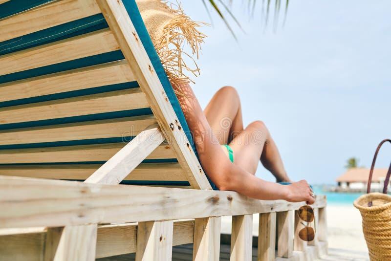 Женщина на пляже на деревянных loungers шезлонга стоковые фото