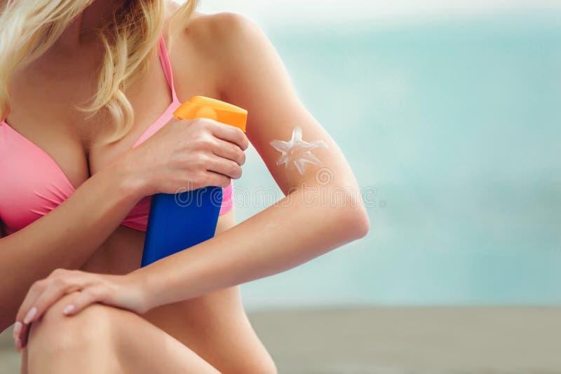 Женщина на пляже прикладывая creme блока солнца стоковое изображение rf